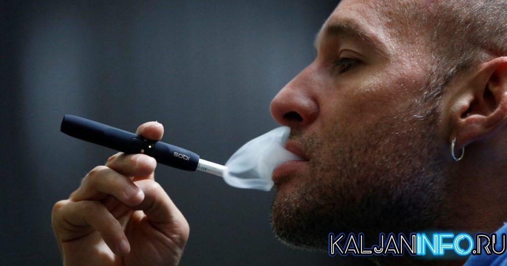 Мужчина курит Айкос.