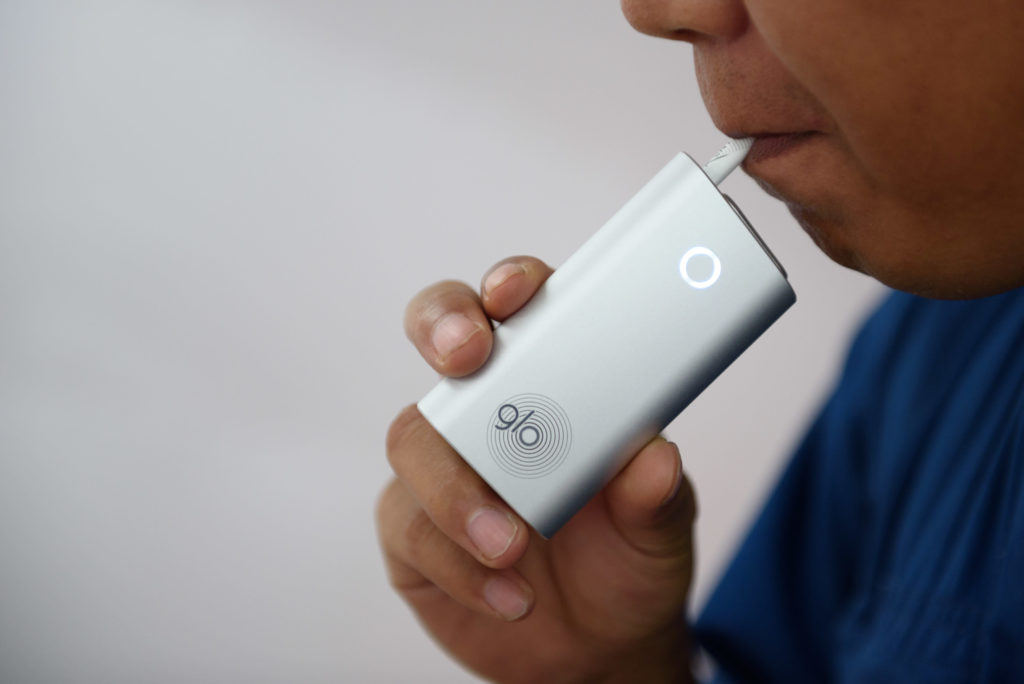Человек курит glo.