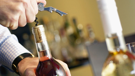 Мужчина открывает бутылку вина